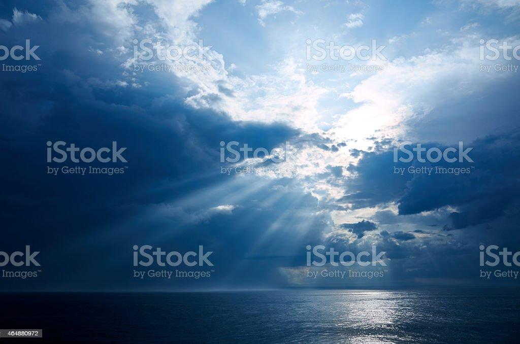 Sunset, sun rays on dark cloudy sky stock photo