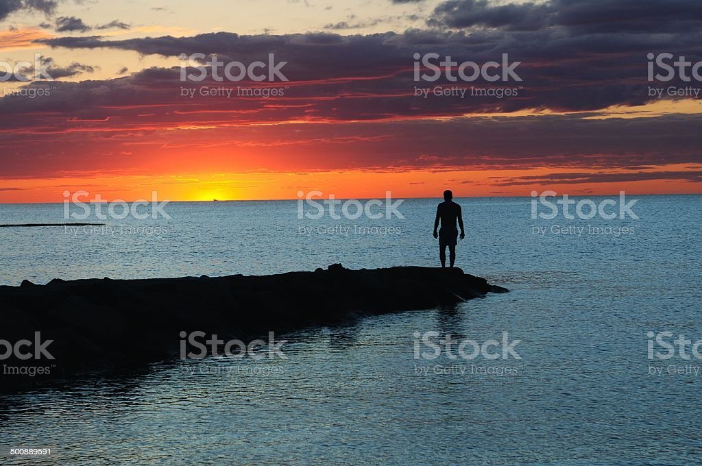 sunset sunrise beach solo man on the shoreline stock photo