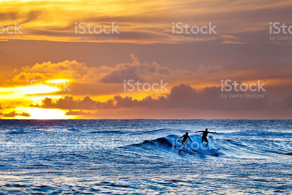 Sunset Surfers Surfing Scenic Hawaiian Ocean off Poipu Beach, Kauai stock photo
