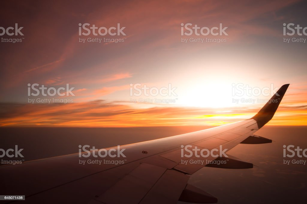 Sunset time and flare with airplane wing from the inside. stock photo