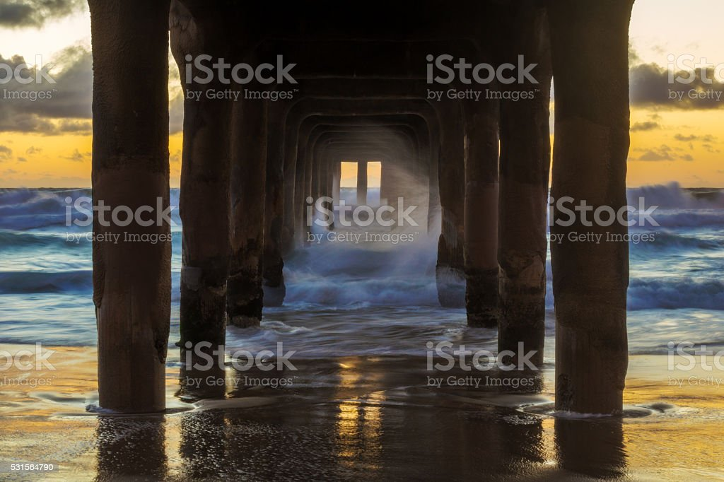 Sunset Under a Pier on the Ocean stock photo