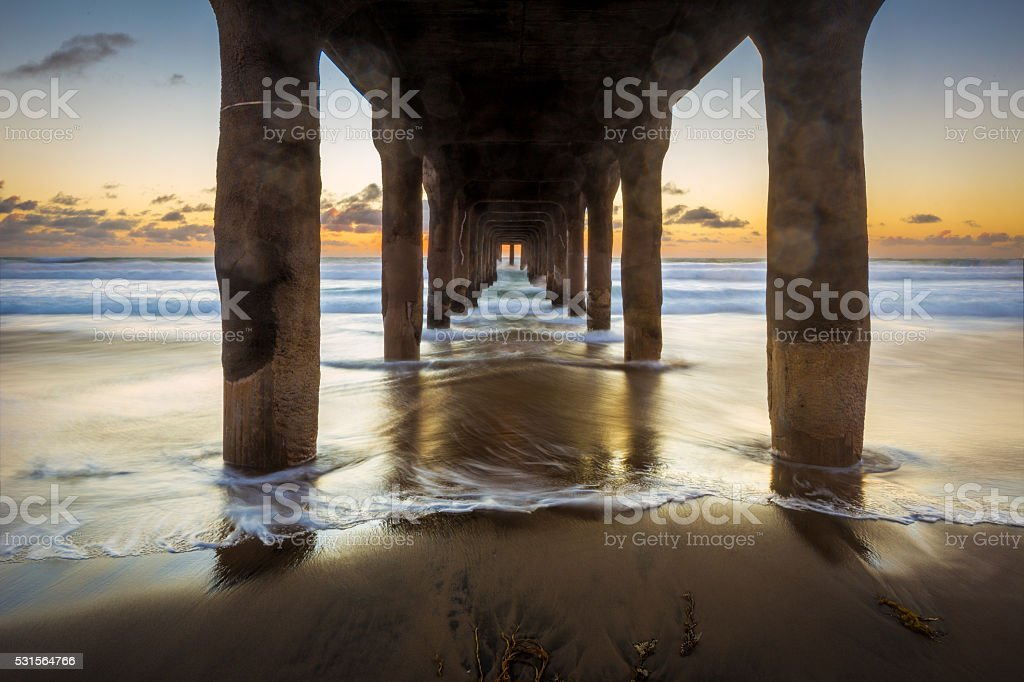 Sunset Under a Pier on the Ocean with Waves stock photo