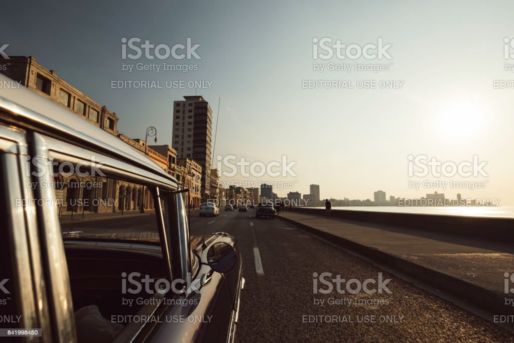 Sunset view of urban cityscape Havana skyline and ocean from inside taxi stock photo