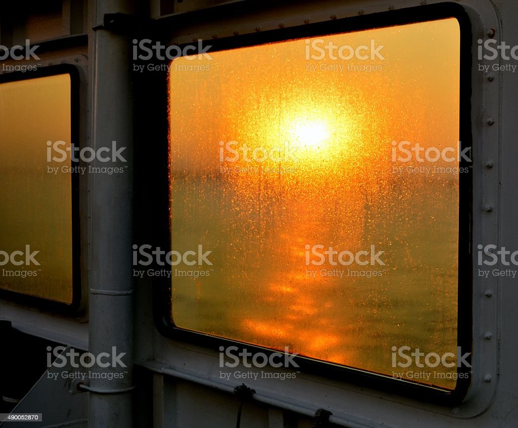 Sunset view through the windows of a ferry. stock photo