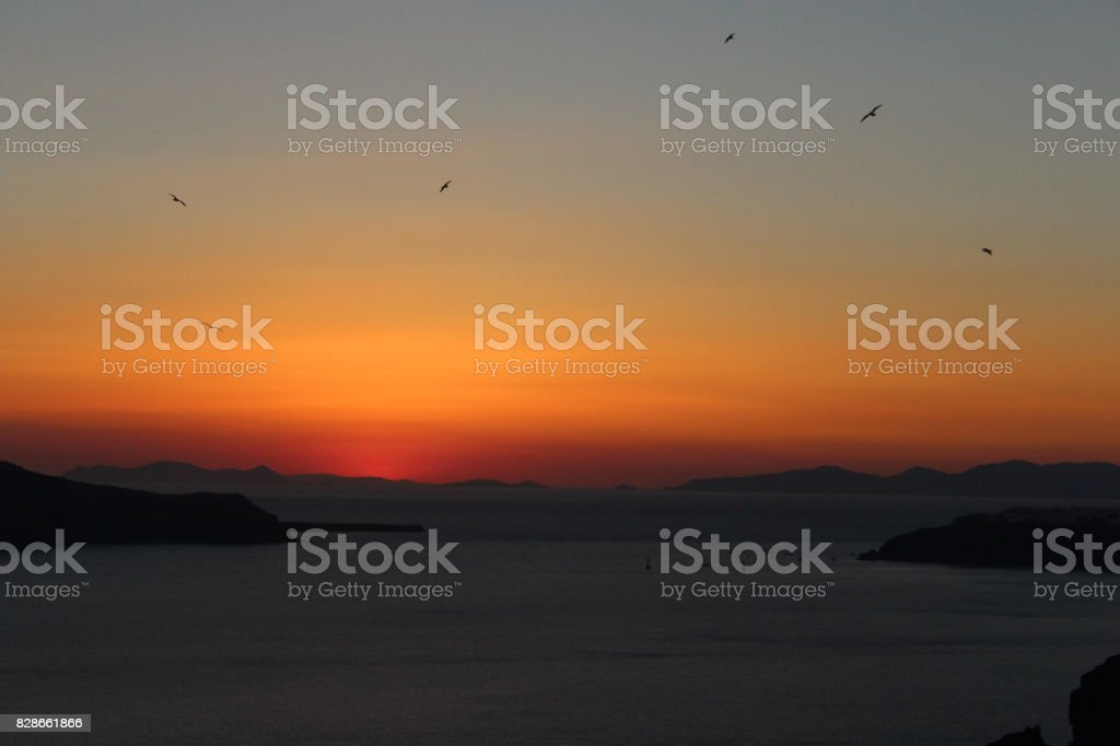 Sunset Views in the Greek Island of Santornini with Birds Flying stock photo