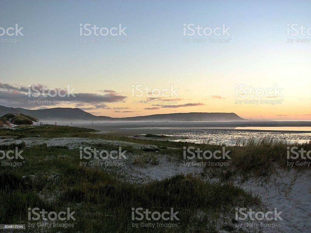 Sunset walkers on Noordhoek Beach, Cape Town stock photo