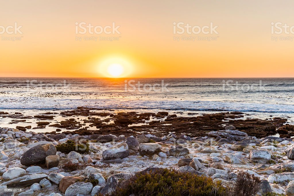 Sunset waves at the beach with white boulders stock photo