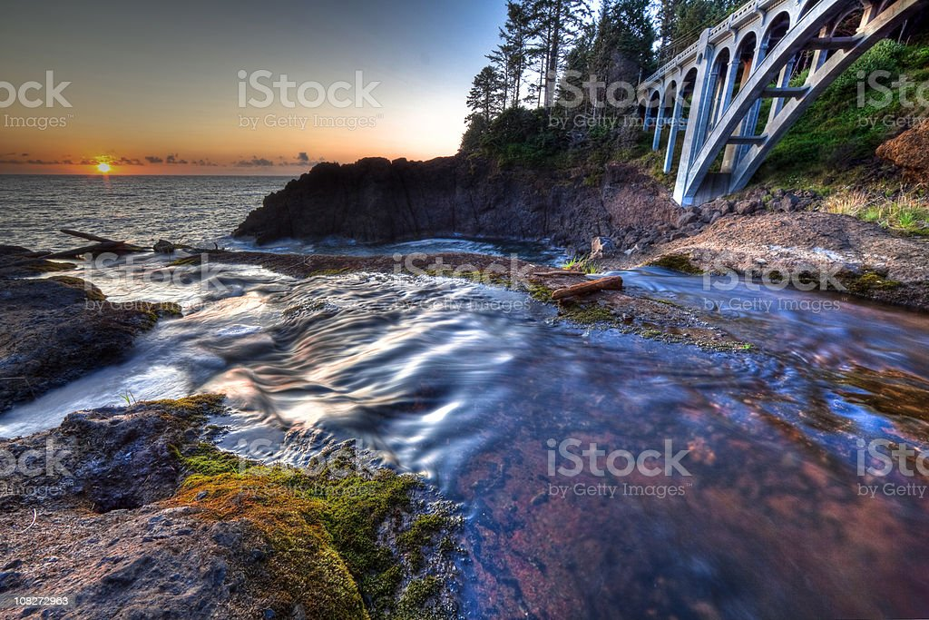 Sunset with a creek, moss, and bridge on the ocean royalty-free stock photo