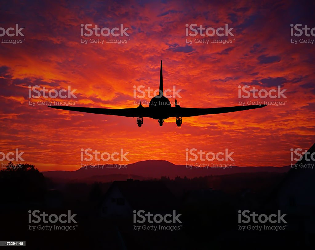 Sunset with a plane silhouette stock photo