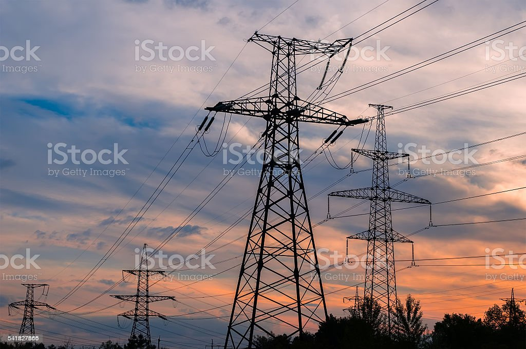 sunset with a silhouette of electricity pylon and power lines stock photo