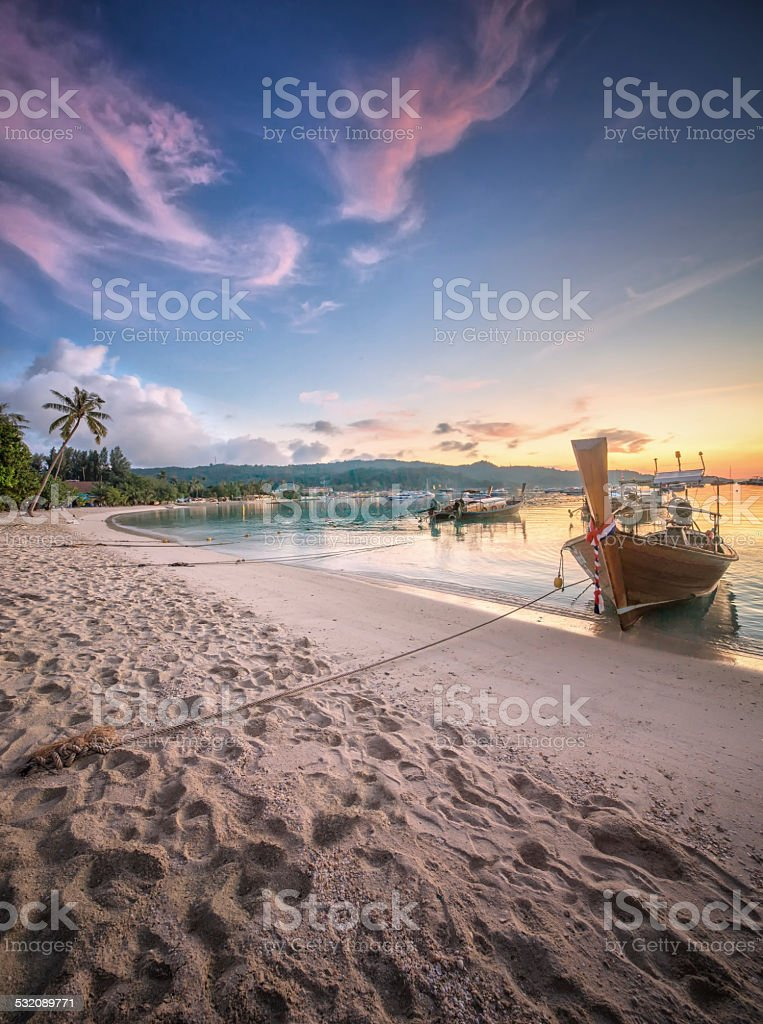 sunset with colorful sky and boat on the beach stock photo