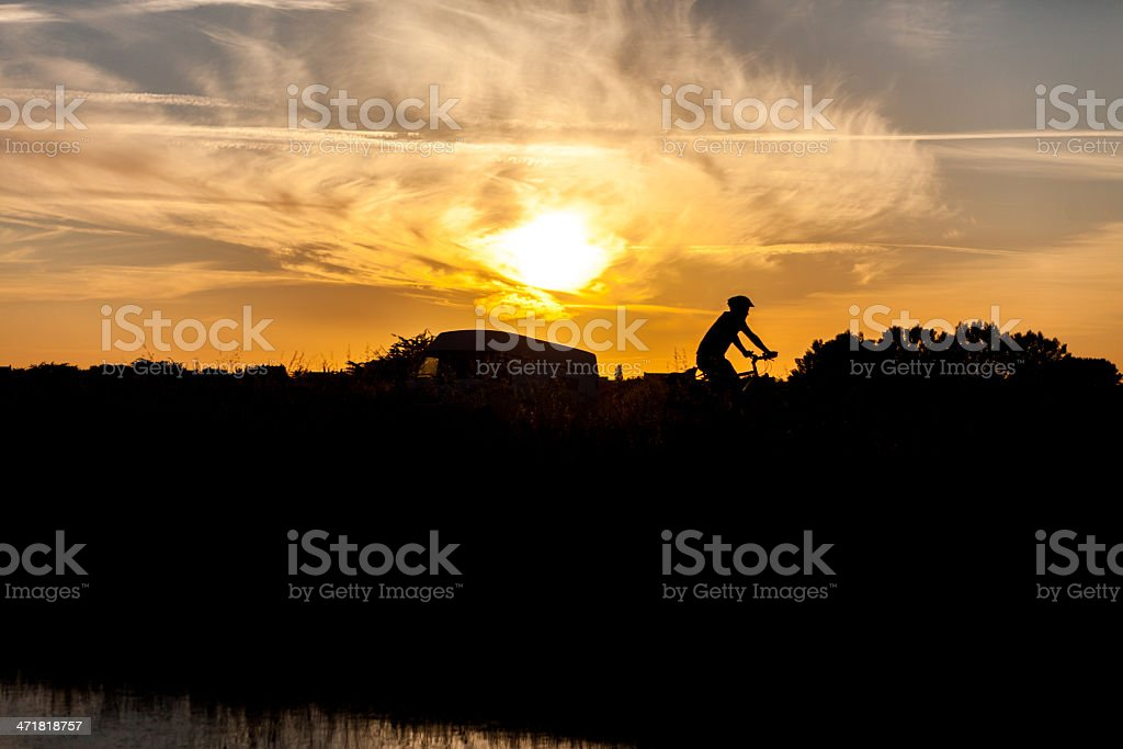 sunset with cyclist shadow stock photo