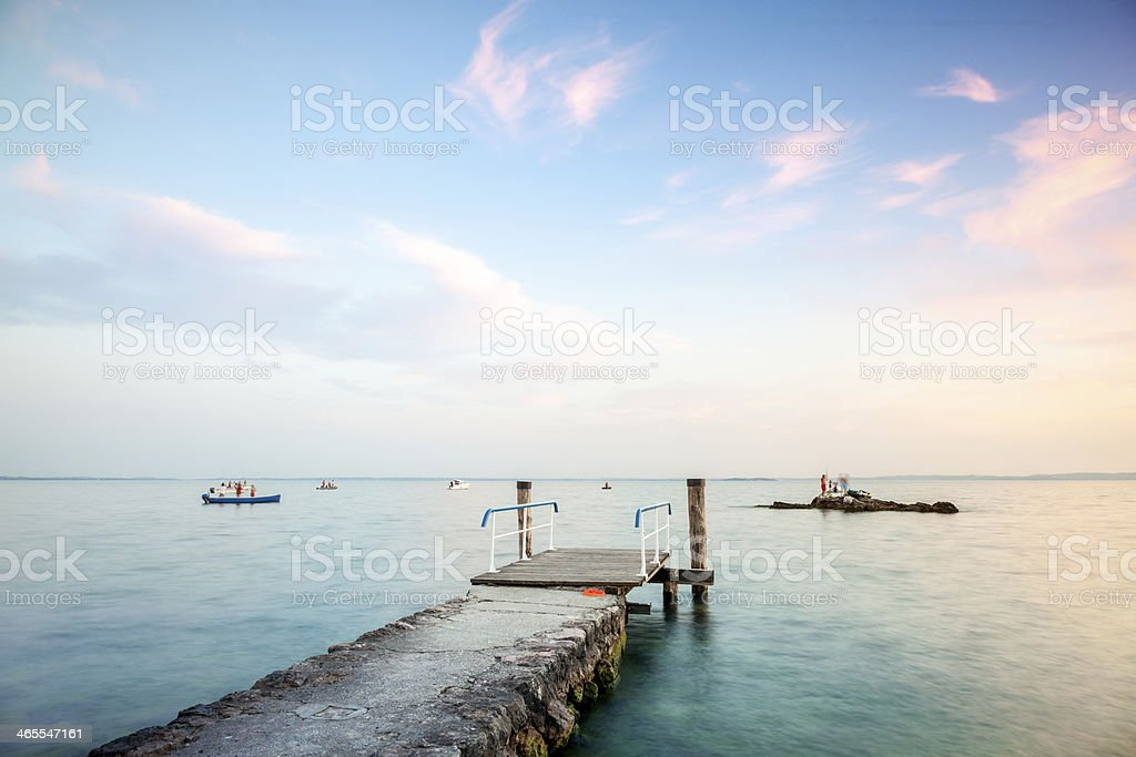 sunset with fishing boats and pier royalty-free stock photo