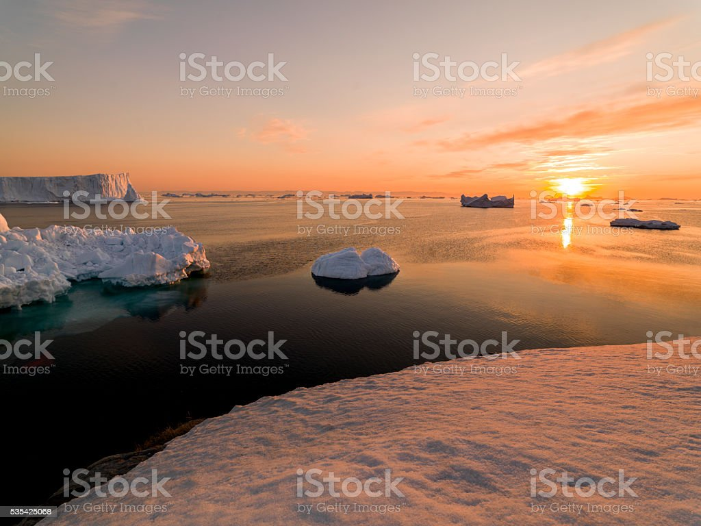 Sunset with icebergs in north pole, ilulissat disco bay, Greenland stock photo