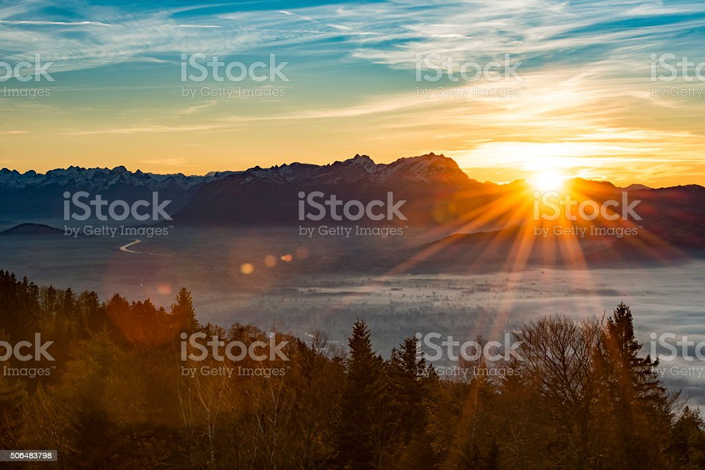 sunset with lens flares at the swiss mountains stock photo