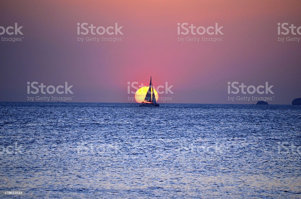 Sunset with sail boat at the ocean stock photo