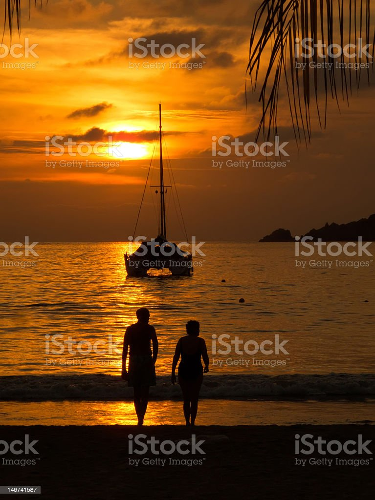 Sunset with sailboat and couple silhouetted stock photo