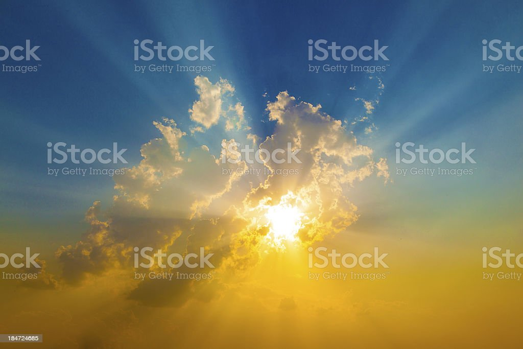 Sunset with sun rays coming through clouds stock photo