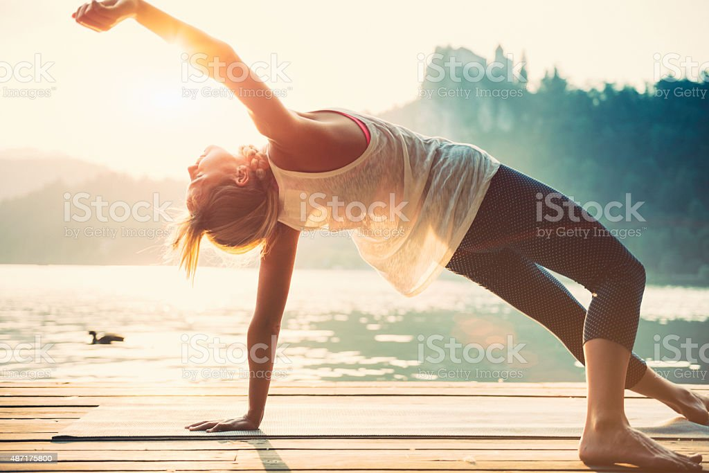 Sunset Yoga by the water stock photo