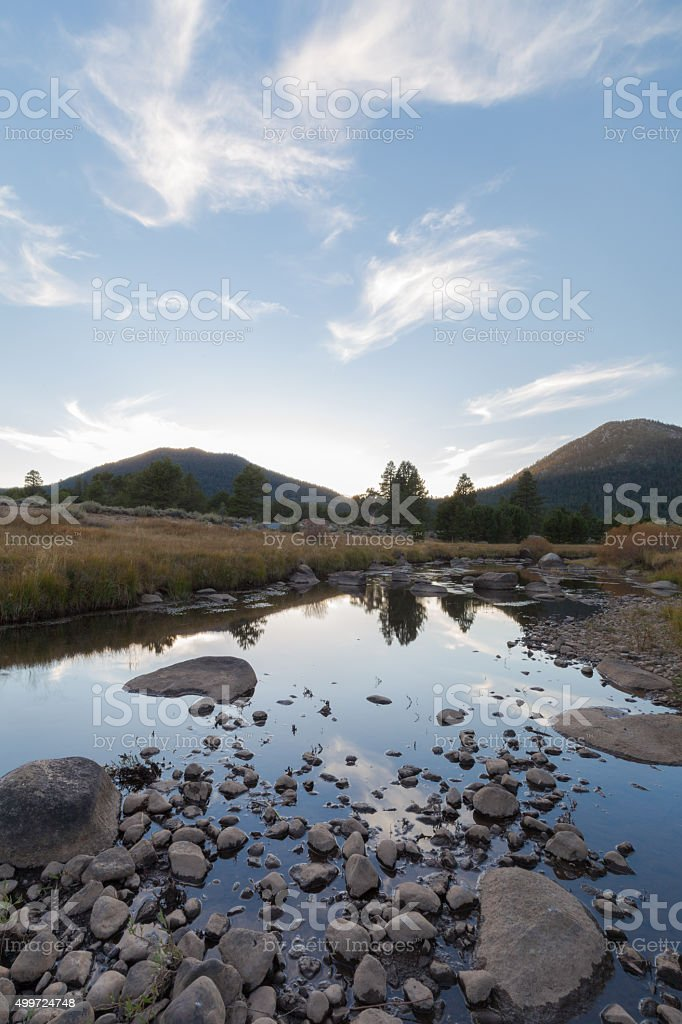Sunsetting on a alpine valley with a river and mountains stock photo