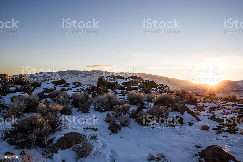 Sunsetting over distant mountains stock photo
