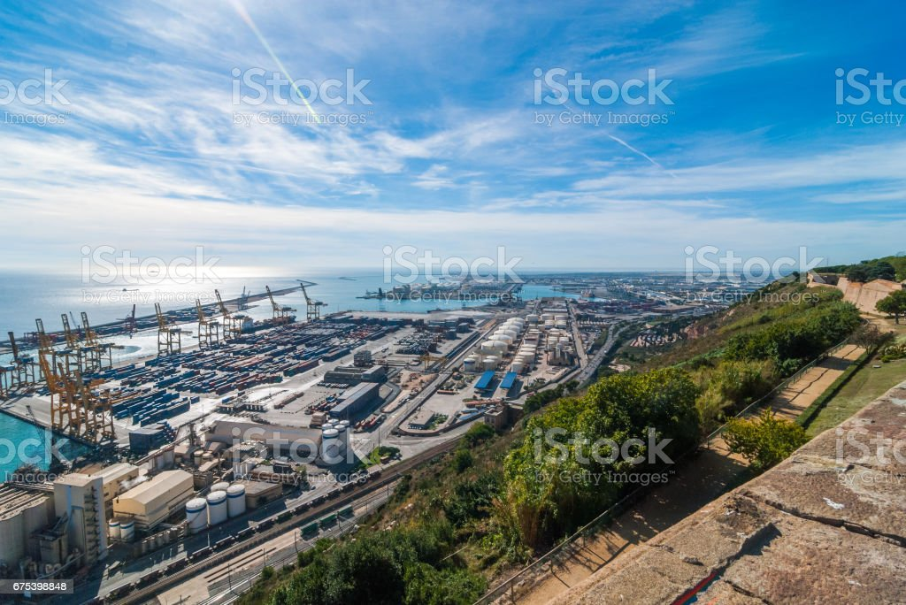 Sunshine on Balearic sea & Barcelona industrial shipping and rail ports on a blue-sky day. stock photo