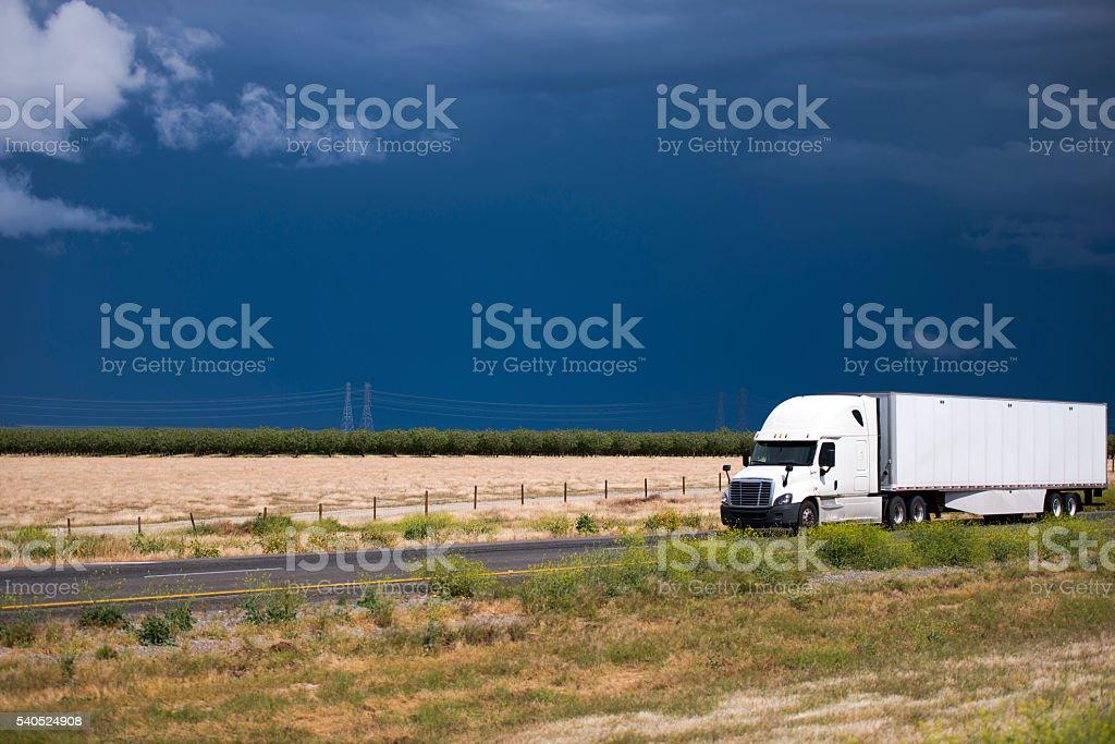 Sunshine semi truck on California road and dark clear sky stock photo