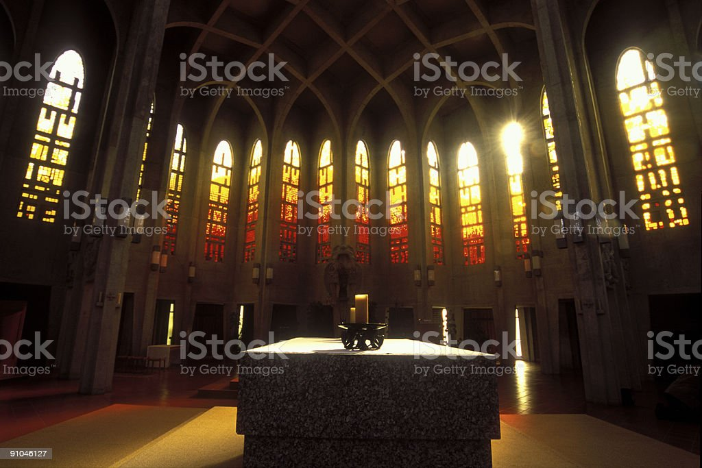 Sunshine through stained glass on draped altar with candles stock photo