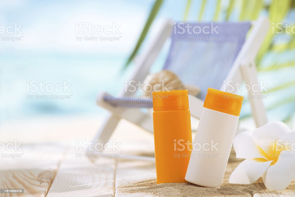 Suntan lotion, deck chair and plumeria flower with copy space royalty-free stock photo