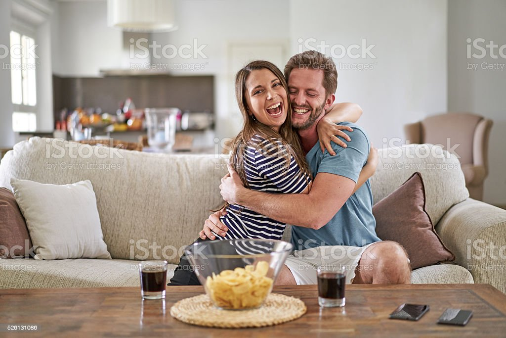 super happy couple on their couch celebrating something like soccer stock photo