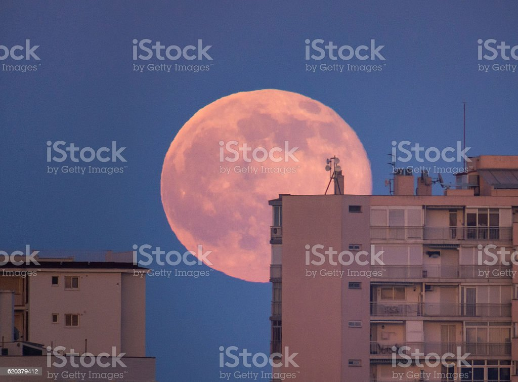 red full moon behind building