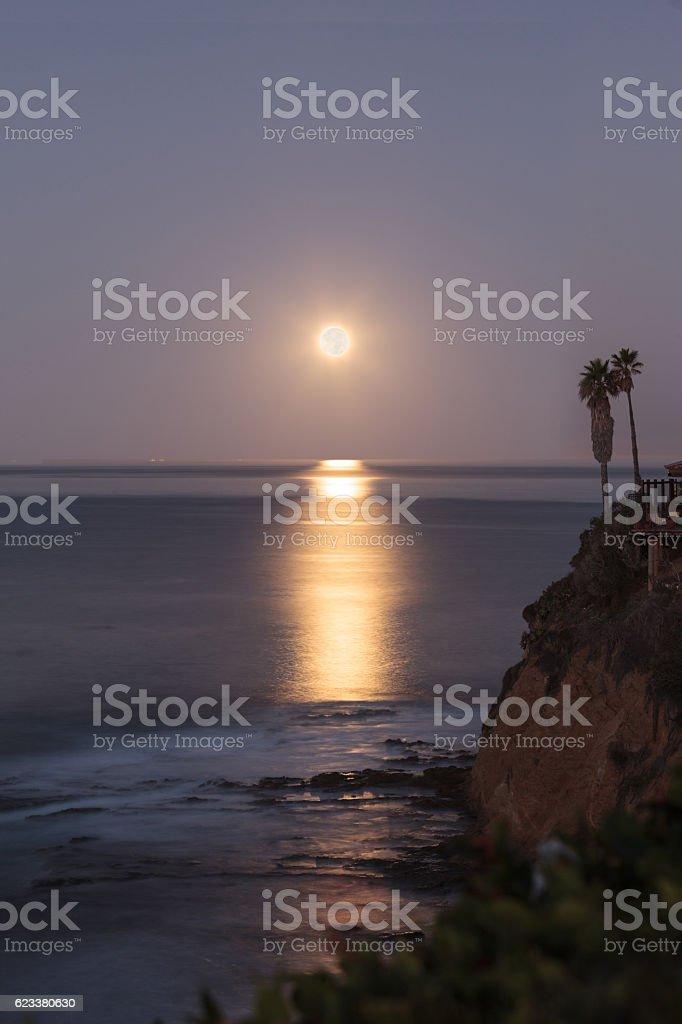 Super moon sets over the Pacific ocean in Laguna Beach stock photo