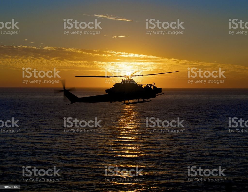 AH-1 Supercobra flying over ocean at sunset stock photo