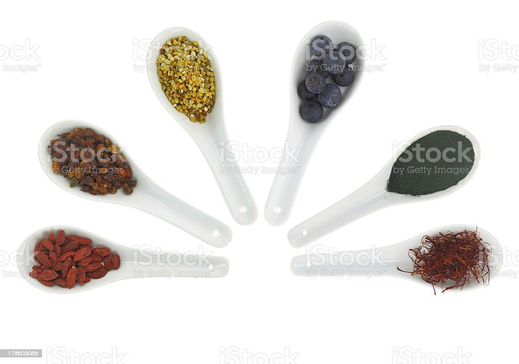 Superfoods in porcelain spoons. Pollen, goji berries, blueberrie royalty-free stock photo