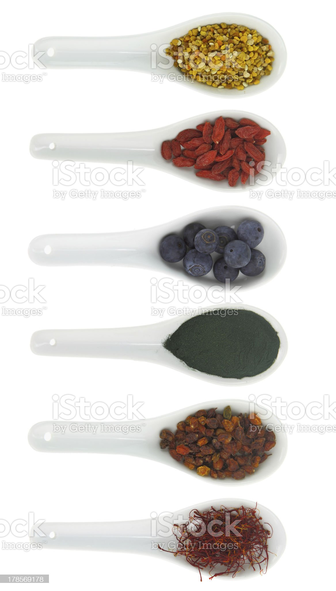 Superfoods in porcelain spoons. Pollen, goji berries, blueberries, spirulina royalty-free stock photo