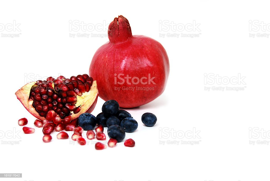 Superfruits: pomegranate and blueberries on white background royalty-free stock photo