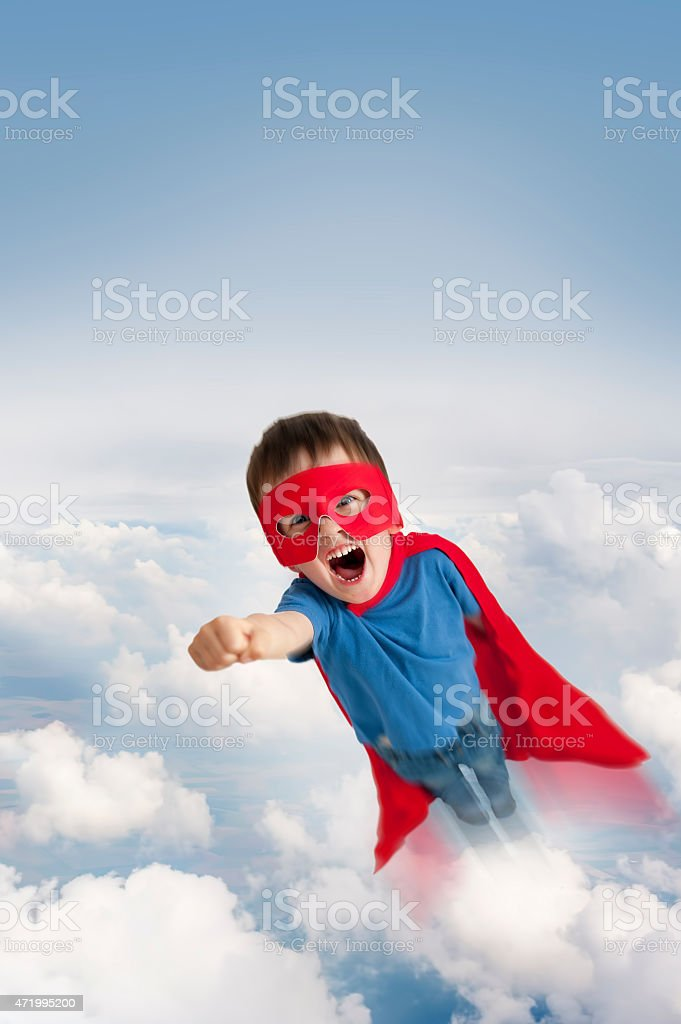 superhero boy flying in the sky stock photo