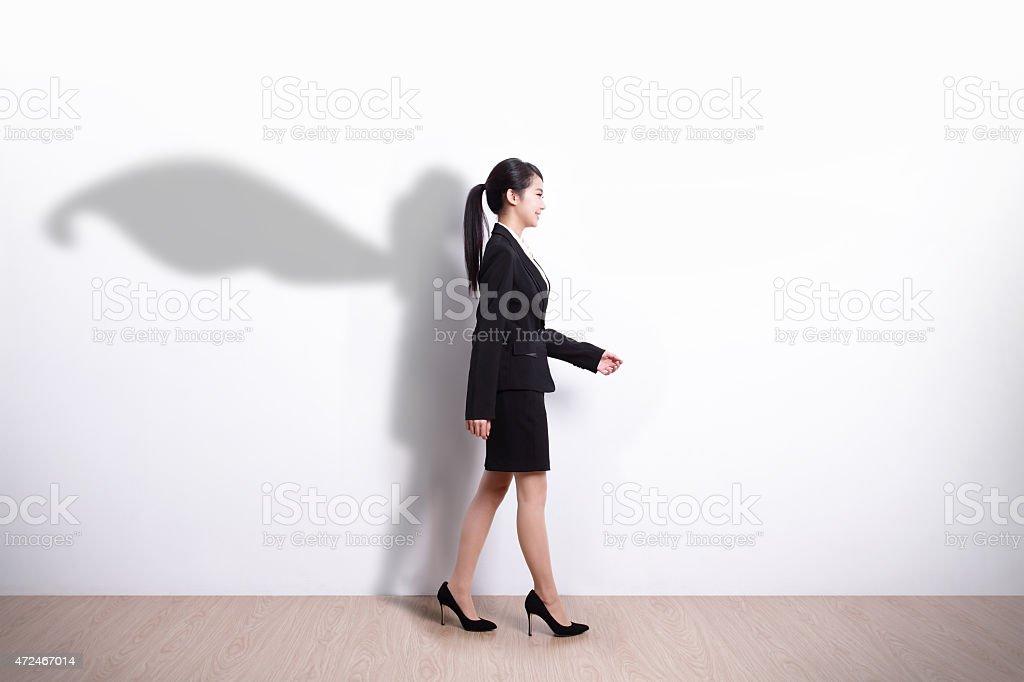 Superhero business woman walking stock photo