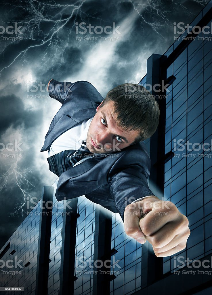 Superhero businessman flying over downtown royalty-free stock photo