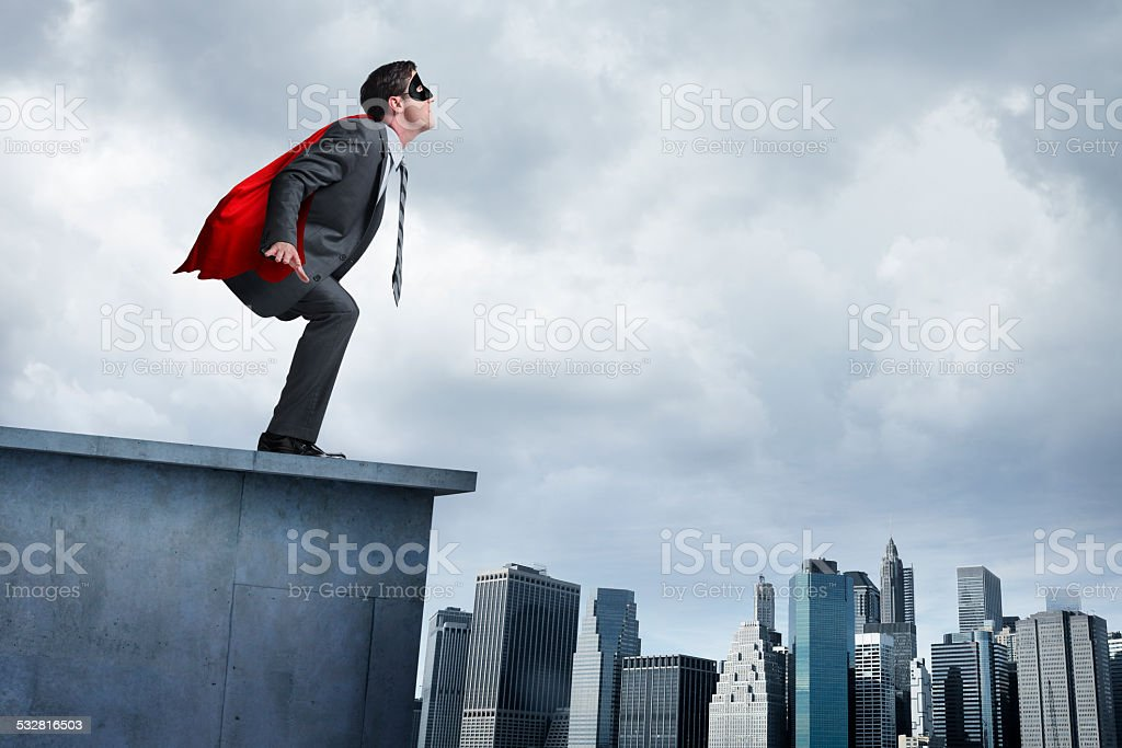 Superhero businessman in red cape attempting to take flight stock photo