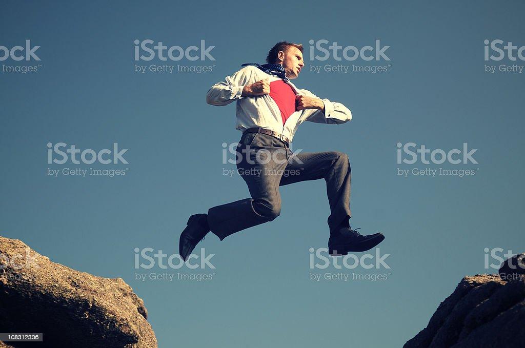 Superhero Businessman Jumping Outdoors above Rocks royalty-free stock photo