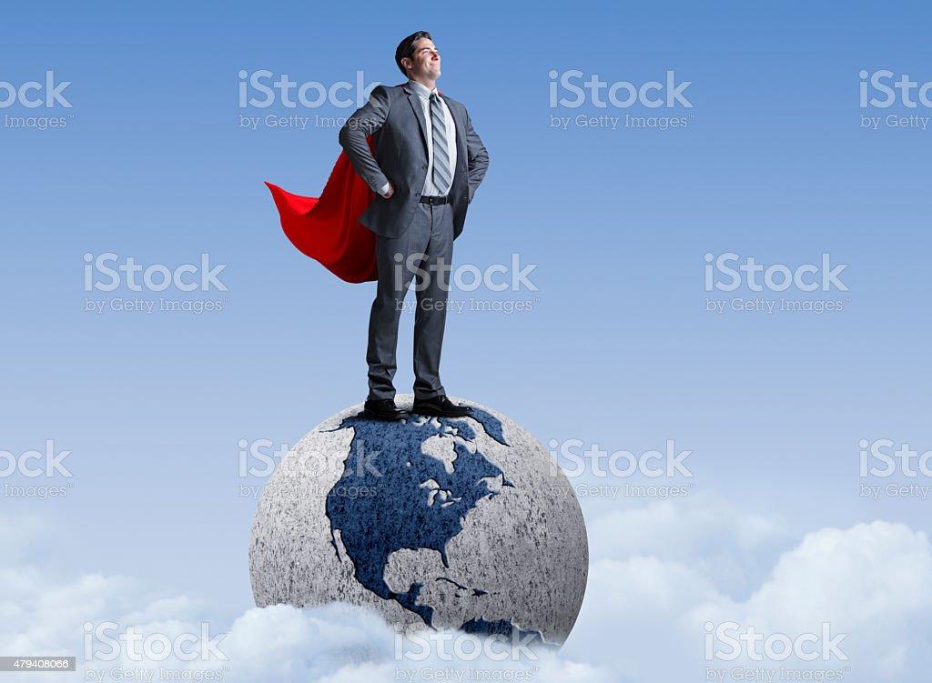Superhero Businessman Standing On Globe stock photo