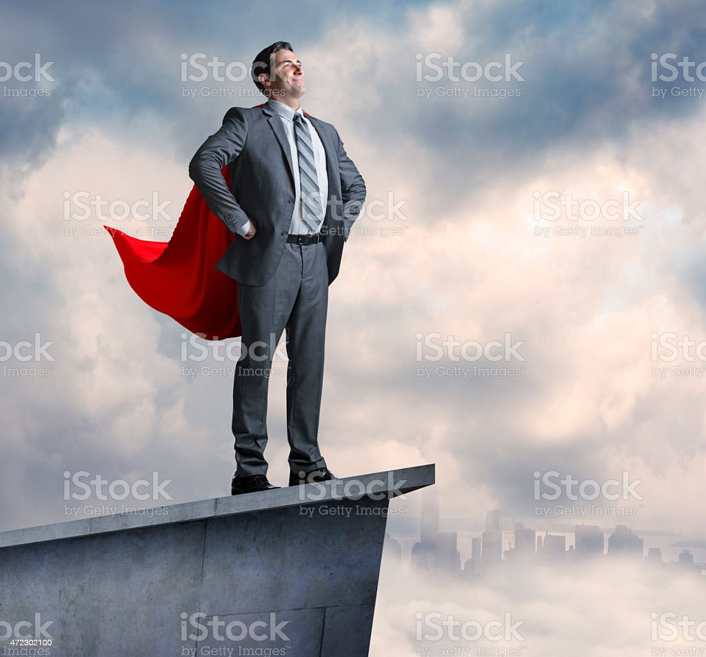 Superhero businessman standing on promontory with city in distance stock photo