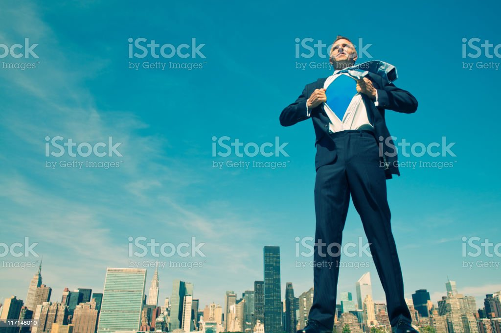 Superhero Businessman Standing Tall and Ready Above City Skyline stock photo
