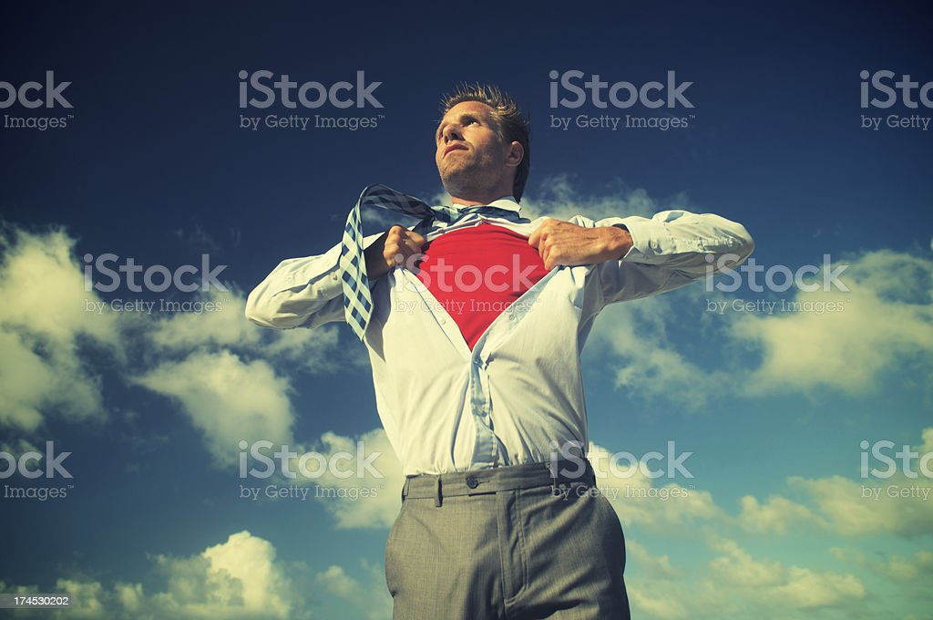 Superhero Businessman Transforming in Bright Blue Sky stock photo