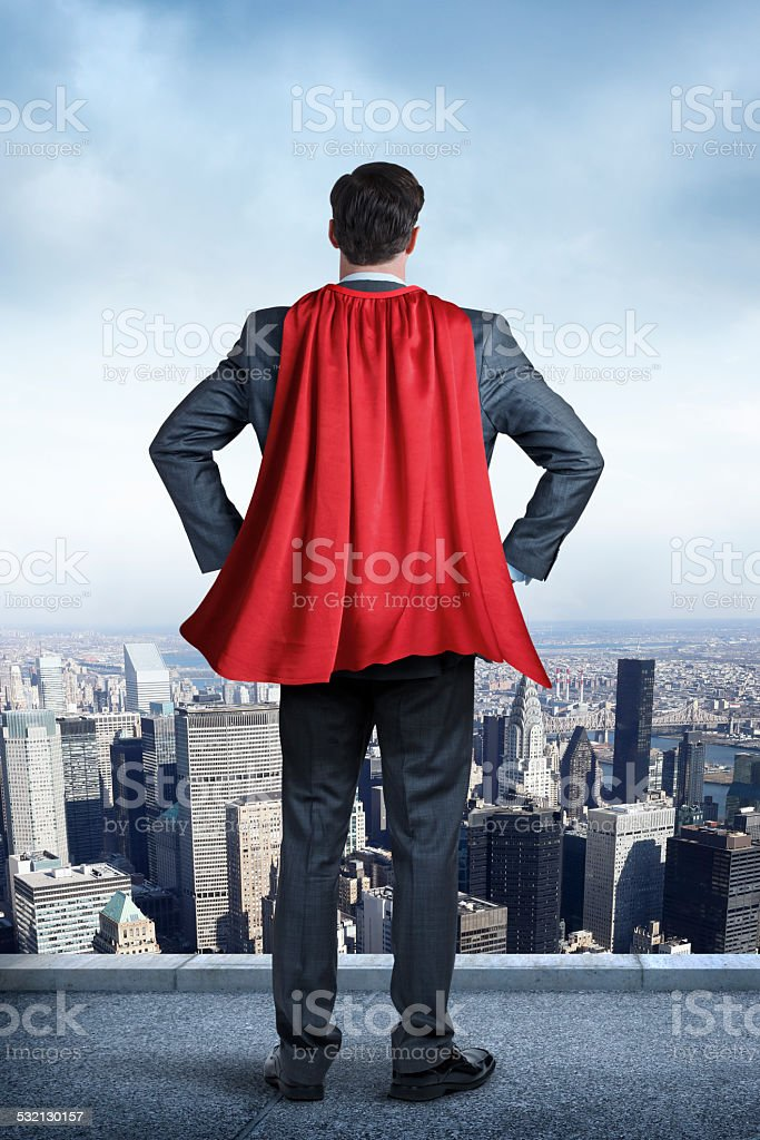 Superhero Businessman Wearing Red Cape Looking At Big City stock photo