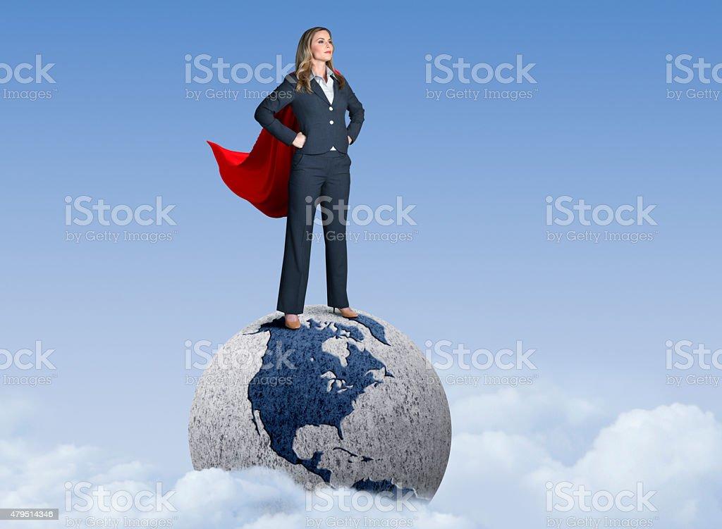 Superhero Businesswoman Standing On Globe stock photo