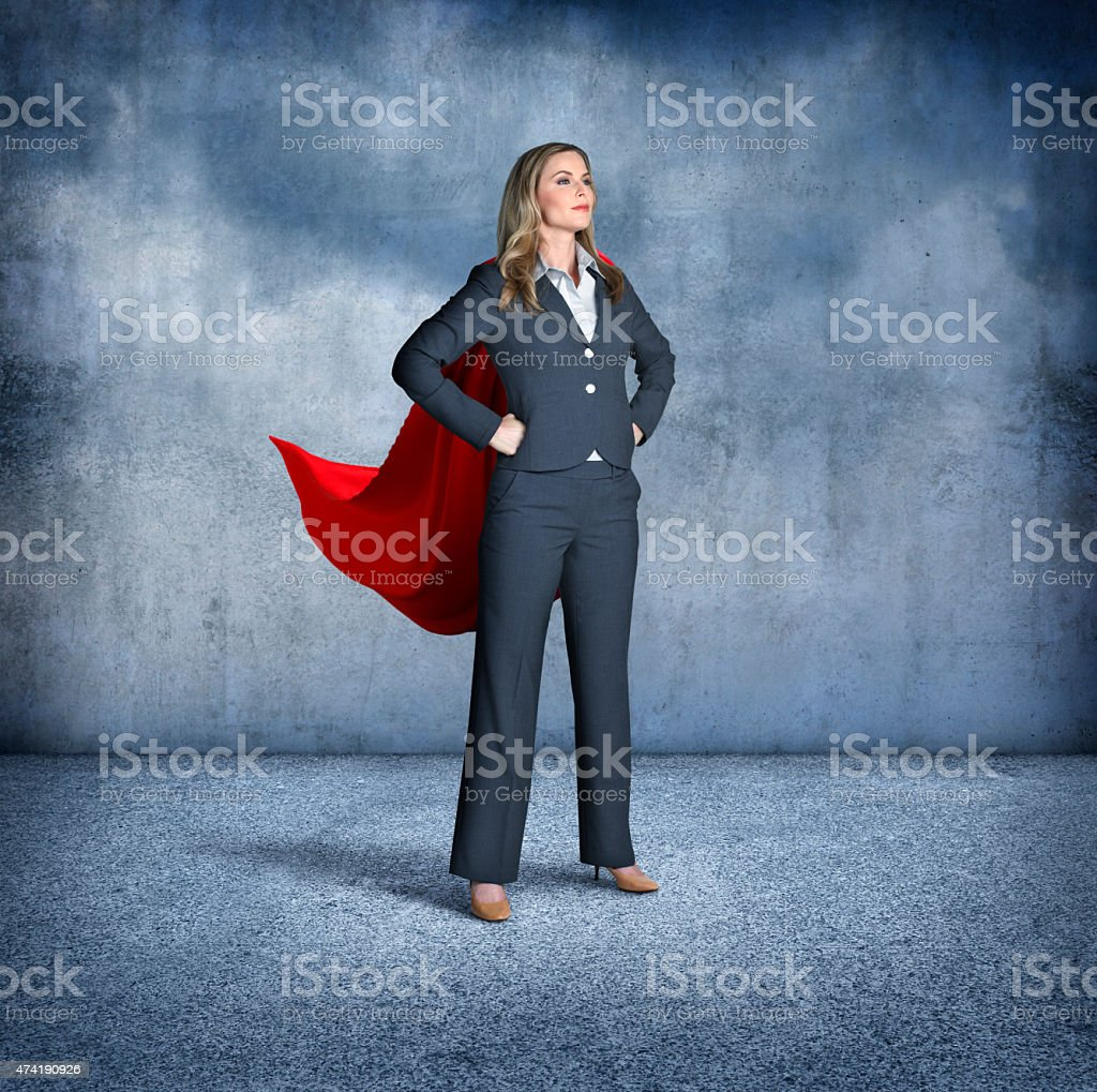 Superhero businesswoman standing with hands on her hips stock photo