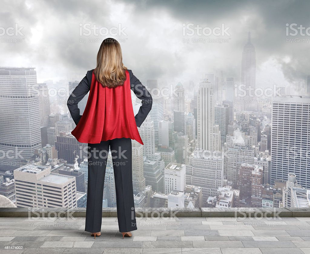 Superhero Businesswoman Wearing Red Cape Looking At Big City stock photo