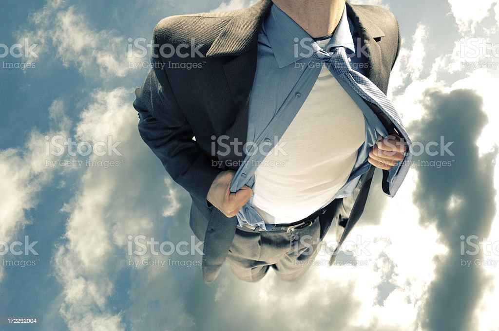 Superhero flying in cloudy sky and pulling open his shirt stock photo